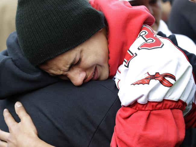 A student wearing a Marysville Pilchuck football jersey is comforted as investigations continue into the tragedy.