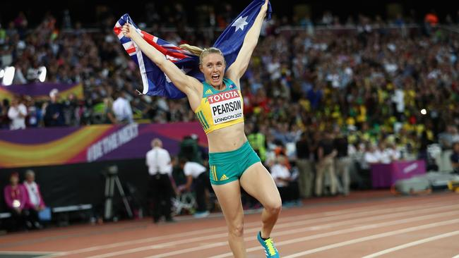 Sally Pearson of Australia celebrates with an Australian flag after winning gold in the Women's 100 metres hurdles final.