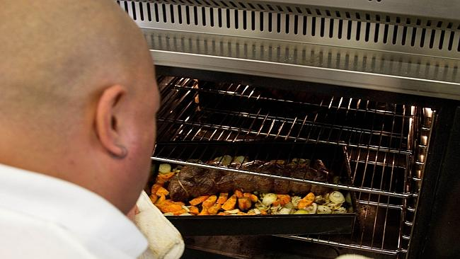 An inmate checking a dish in the oven. Picture: AFP Photo/Marty Melville