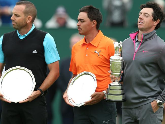 Spain's Sergio Garcia (L) and US golfer Rickie Fowler stand with their second place trophies beside Northern Ireland's Rory McIlroy.