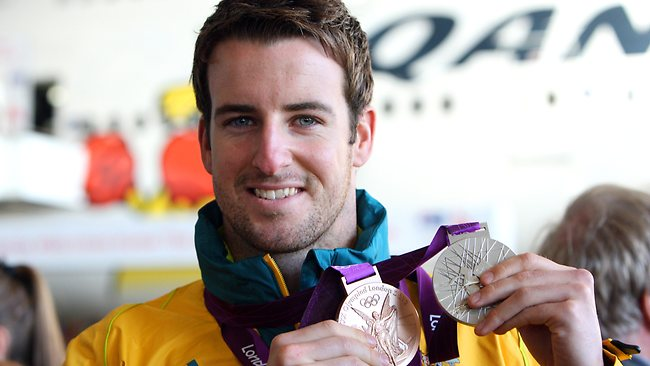 Swimmer James Magnussen shows off his medals after arriving home. Picture: Brad Hunter