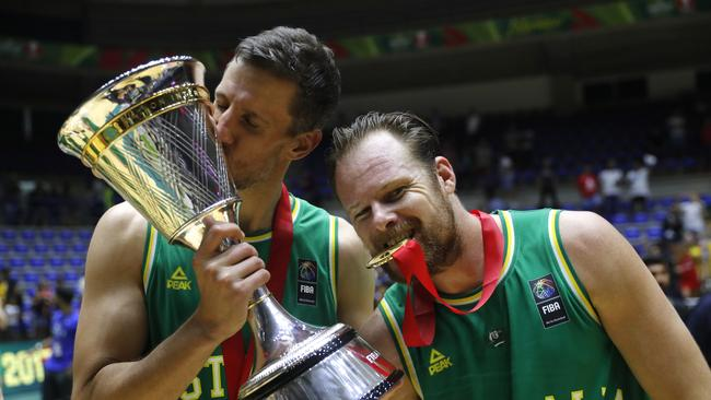 Australia players Daniel kickert and Brad Newley celebrate with the championship trophy. Picture: AP Photo/Hussein Malla