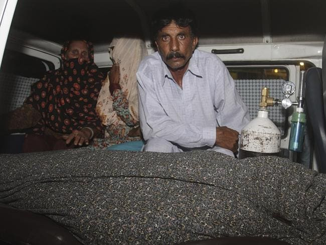 Murdered ... Iqbal sits in an ambulance next to the body of his wife on the day of the stoning attack.