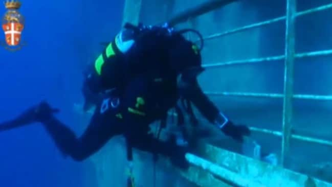 Spooky mission ... a diver enters the  <i>Costa Concordia </i>to inspect what can be salvaged.