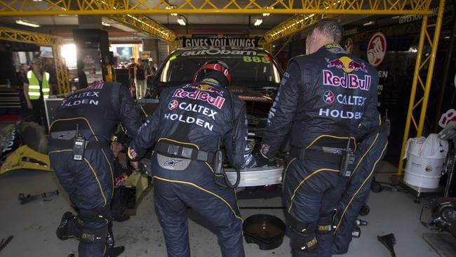 Lowndes's crew working furiously to repair his car.