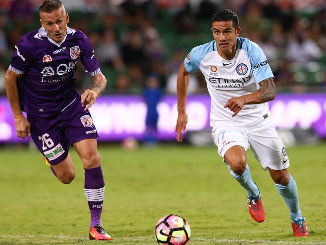 Melbourne City's Tim Cahill (right) gets ahead of Perth Glory's gainst Lucian Goian on Sunday.