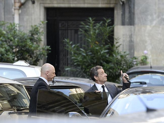 Spoken ... Nicolas Sarkozy (right) gestures as he gets into a car outside his offices in central Paris after an interview with French radio network Europe 1 and French TV channel TF1.
