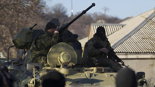 Russian soldiers sit atop an APC as it drives toward the Belbek airbase gate, outside Sev