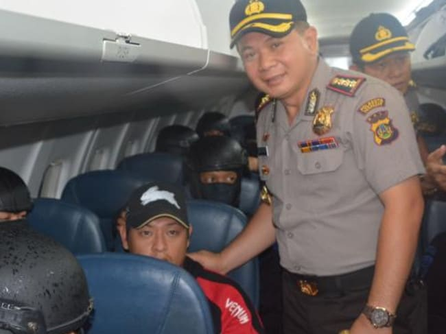 Final humiliation ... an Indonesian official poses for a photo with Bali Nine ringleader Andrew Chan at Bali airport.