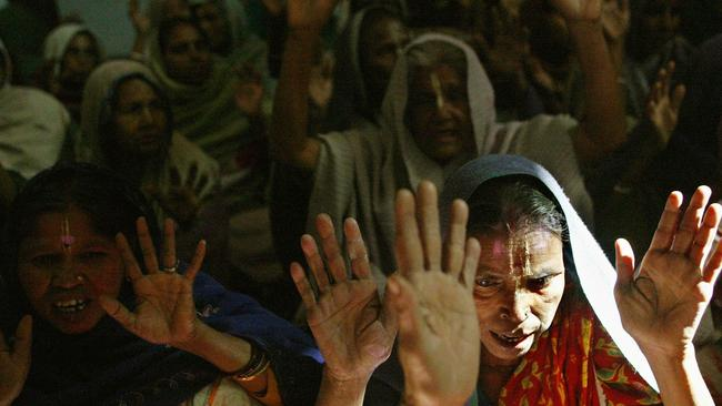 Indian women pray together for more than six hours each day at a temple in Vrindavan, India.