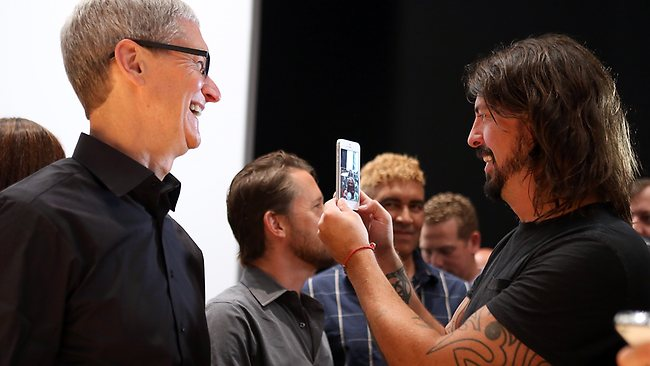 Apple CEO Tim Cook looks on as Dave Grohl of the Foo Fighters examines the new iPhone 5. Picture: Justin Sullivan