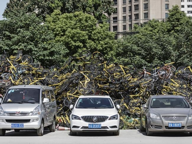Cars sit parked in front of a pile of ride-sharing bicycles in Shanghai, China. Picture: Qilai Shen/Bloomberg via Getty Images
