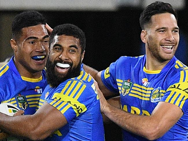 Kirisome AuvaÕa, (left), celebrates with Michael Jennings and Corey Norman after scoring a try of the Eels is tackled by x of the Broncos during the Round 21 NRL match between the Parramatta Eels and the Brisbane Broncos at ANZ Stadium in Sydney, Friday, July 28, 2017. (AAP Image/Dan Himbrechts) NO ARCHIVING, EDITORIAL USE ONLY