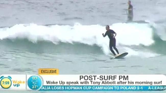 PM hangs ten: Tony Abbott surfing at Queenscliff beach in Manly.
