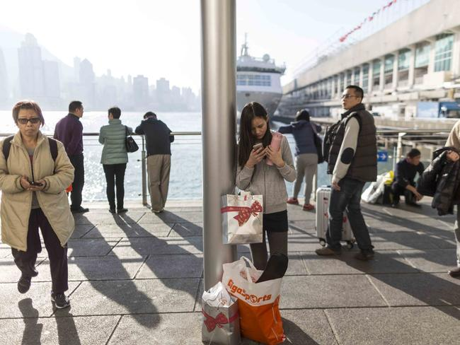 A woman uses her mobile phone and stands by her shopping bags on the Victoria Harbour waterfront in Hong Kong. 'Bobbie' has been an overwhelming success in China with a remarkable following.
