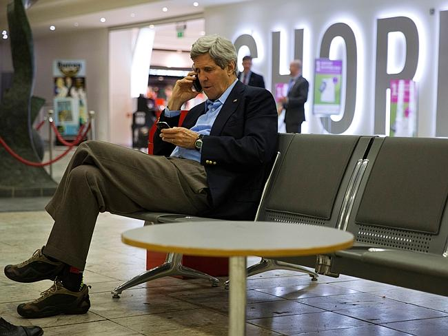 On the job ... US Secretary of State John Kerry arranges on his phone a meeting with Russian Foreign Minister Sergey Lavrov in Paris, while on a refuelling stop at Shannon Airport in Ireland. Picture: Jacquelyn Martin