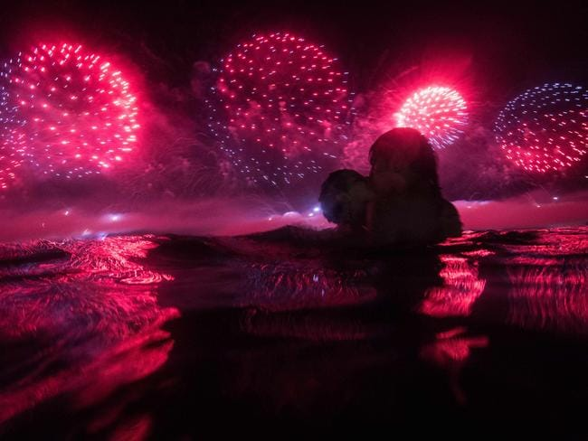 A couple watches fireworks ... at Copacabana beach in Rio de Janeiro on January 1, 2016. Picture: AFP