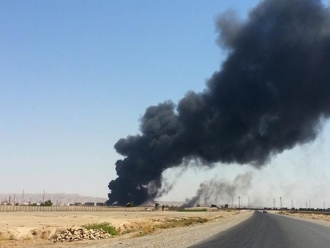 Lawlessness ... a column of smoke rises from an oil refinery in Beiji, some 250km north of Baghdad.