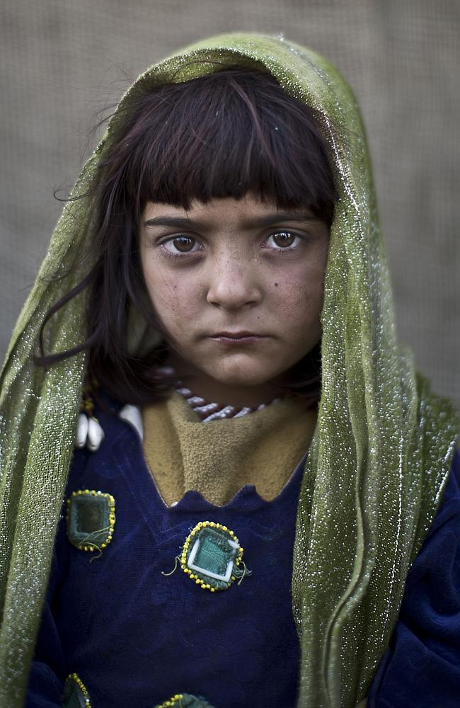 Afghan refugee girl, Zarlakhta Nawab, 6, poses for a picture, while playing with other children in a slum on the outskirts of Islamabad, Pakistan.