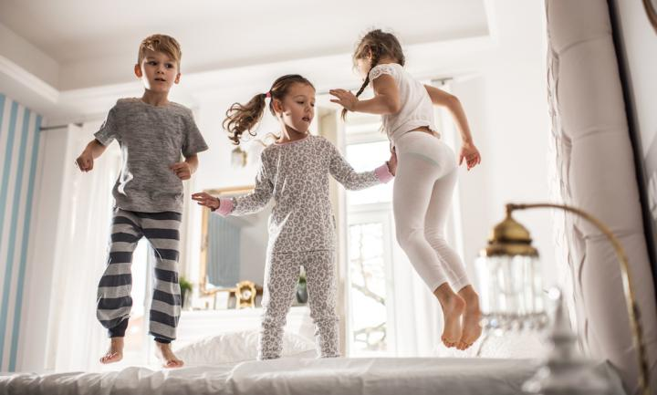Group of children having fun while jumping on a bed.