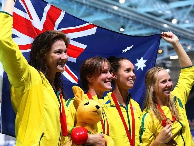 Cate Campbell, Bronte Campbell, Emma McKeon and Melanie Schlanger pose with an Australian flag.