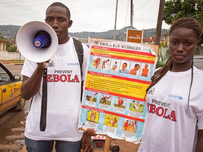 Getting the word out ... a man and woman taking part in a Ebola prevention campaign hold a placard with health information in Freetown, Sierra Leone. Picture: AP Photo/ Michael Duff