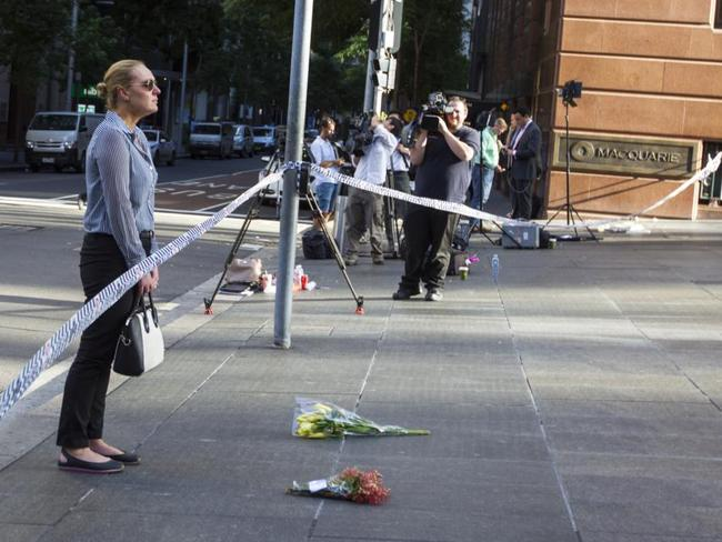 Kate Golder was in tears as she delivered flowers to the scene in Martin Place. Picture by: Kate Dwek / Splash News