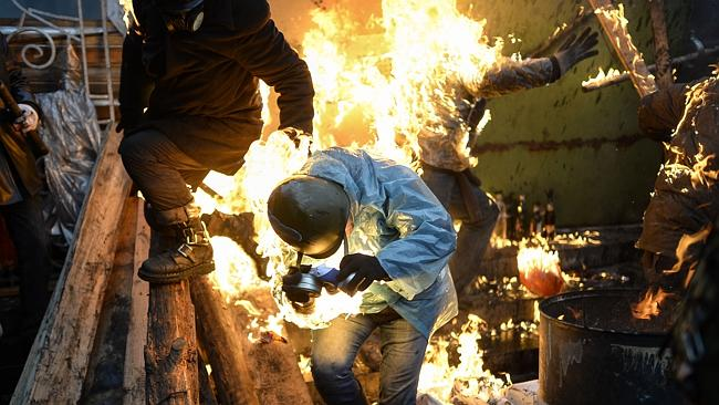 Perils of protest ... Demonstrators burn as they stand behind barricades during clashes with police on February 20 in Kiev. Picture: Bulent Kilic