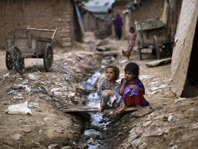 Two girls sit by the door way of a home, in an alley of a slum on the outskirts of Islamabad, Pakistan. Sewage mixing with drinking water is a hotbed for infection. Picture: AP