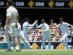 Graeme Swann of England celebrates with teammates Ian Bell and Alastair Cook after catching out Shane Watson.