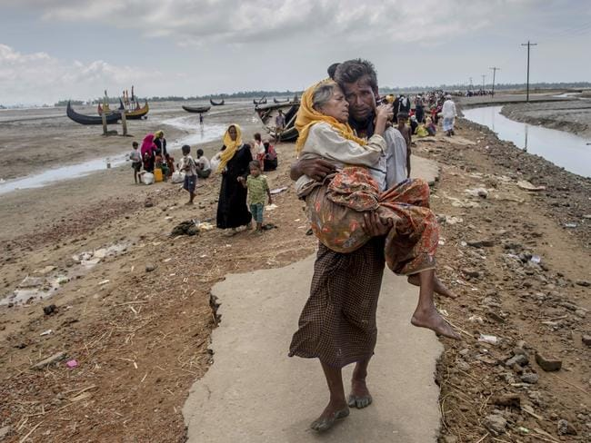 A Rohingya man carries his mother to a refugee camp in Bangladesh. Picture: Dar Yasin