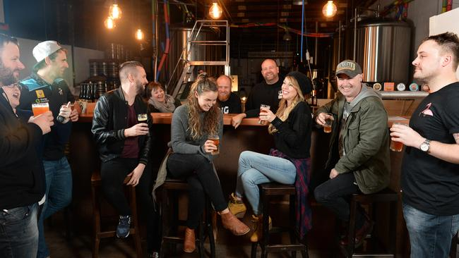 Big Shed owners Craig Basford and Jason Harris (behind the bar) with customers at their Royal Park brewery. Picture Campbell Brodie
