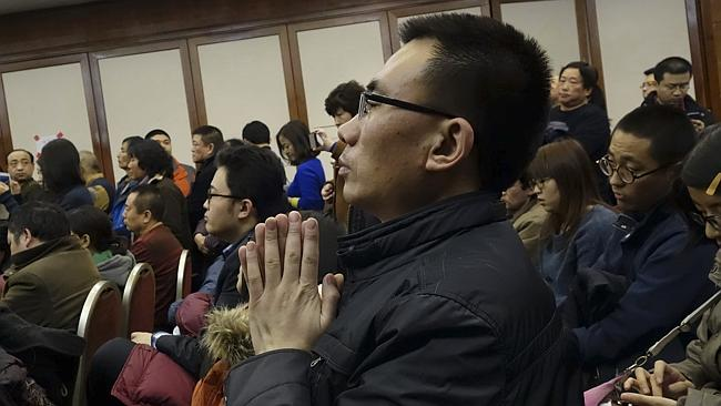 A relative of Chinese passengers aboard missing Malaysia Airlines Flight MH370 prays at a gathering with other passenger families in a hotel in Beijing, China, Monday March 10, 2014. (AP Photo) CHINA OUT