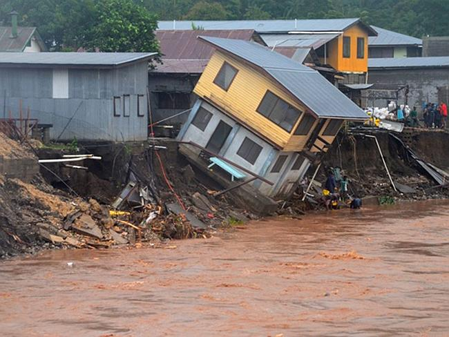 Disastrous ... A building teeters on the edge of a river in Honiara, Solomon Islands after flash floods killed 14 people and left thousands more homeless at the beginning of the month. Pic: AP Photo/Solomon Star