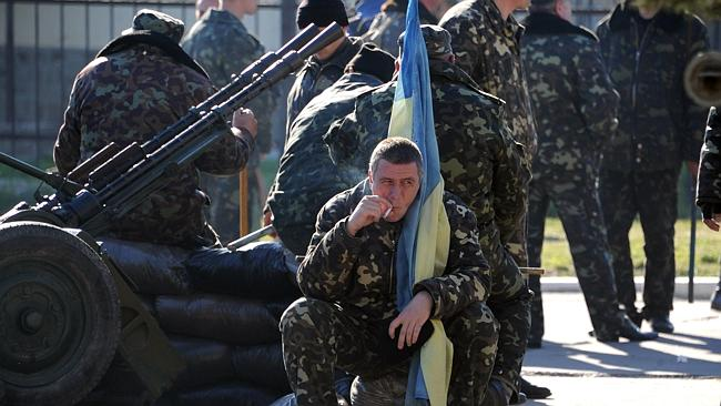 Under siege ... Ukrainian officers brace themselves moments before pro-Russia militia and
