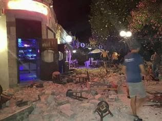 A man lies on the ground as other tourists stand outside a bar after an earthquake on the Greek island of Kos early Friday, July 21, 2017. A powerful earthquake struck Greek islands and Turkey's Aegean coast early Friday morning, damaging buildings and a port and killing at least two people, authorities said. (Kostoday.gr via AP)