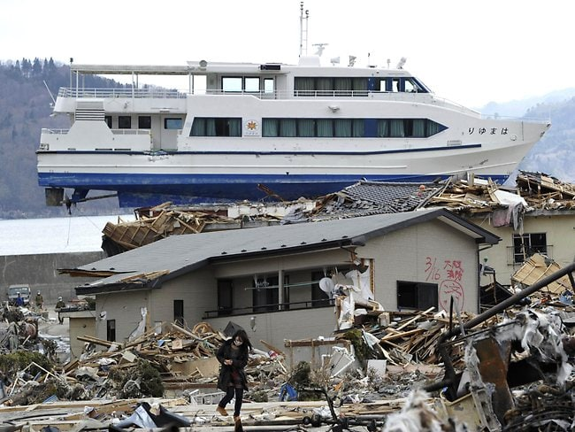 Earthquake aftermath: a Japanese girl searches through the debris as a ship sits atop a building after the March 2011 earthquake and tsunami, which devastated the country's east coast. (AP Photo/Yomiuri Shimbun, Yasuhiro Takami)