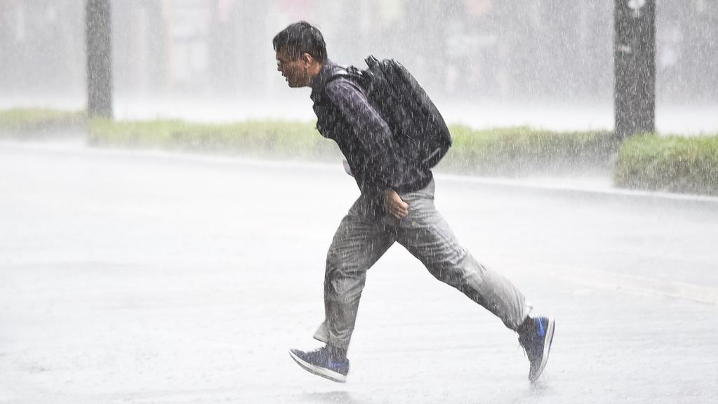 Pedestrian caught in the rain on King William St. Picture: Bernard Humphreys