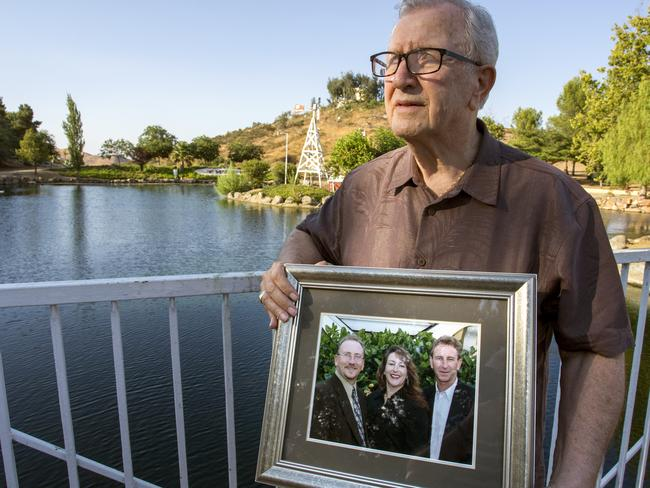 Mr Kerrigan holds onto a photograph of his three children, showing his Frank, far right. Picture: Andrew Foulk/AP