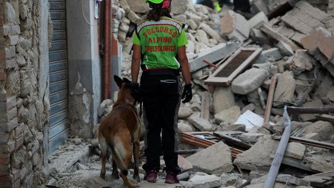 Rescuers search for victims among the rubble of a house. Picture: Filippo Monteforte.