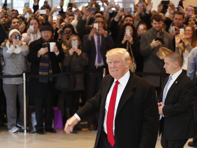 A crowd film President-elect Donald Trump as he leaves the New York Times after a meeting which was called off and then rescheduled. Picture: AP Photo/Mark Lennihan.