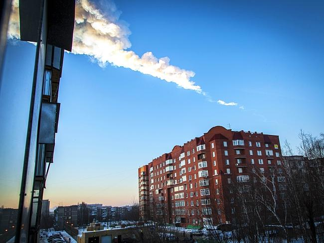 Fire in the sky ... the meteorite trail seen above an apartment block in Chelyabinsk. Pic: Oleg Kargopolov.