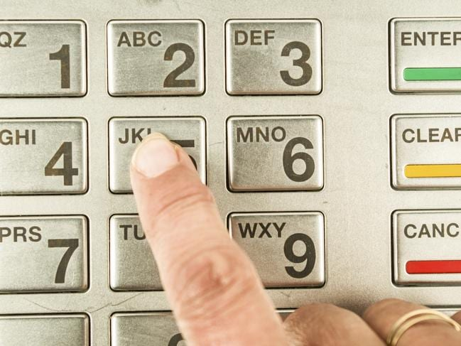 Closeup of finger presssing number five in atm machine with metallic keyboard. Picture: iStock
