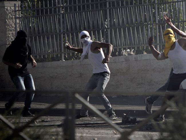 Furious ... masked Palestinian protesters throw stones at Israeli police during clashes in the Shuafat neighbourhood in Israeli-annexed Arab East Jerusalem on July 3. Picture: AFP