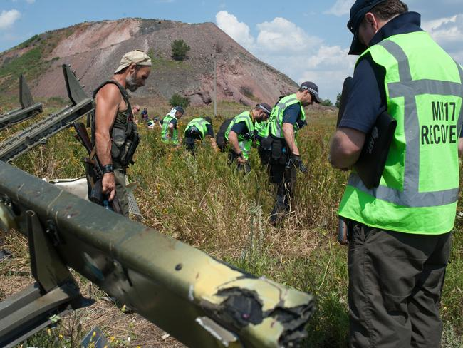 Tense situation ... A pro-Russian rebel, left, guards as Australian, Malaysian and Dutch investigators examine the area of the downed Malaysia Airlines Flight MH17. Picture: AP