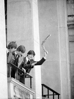Paul McCartney waves a boomerang from the balcony at the Melbourne Town Hall as the band arrives for a state reception. Picture: Herald Sun Image Library