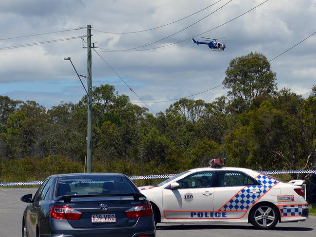 Police officers establish a crime scene near bushland in Kingston, south of Brisbane, as the search continues.