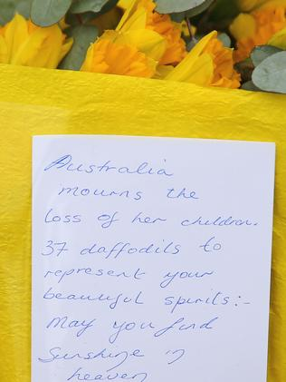 Touching letters ... floral tributes are left at a memorial service held for victims of the MH17 disaster. Picture: Scott Barbour