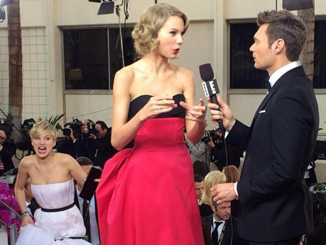 Jennifer Lawrence photobombs Taylor Swift while she's being interviewed by Ryan Seacrest at the Golden Globes. Picture: Supplied