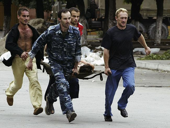Volunteers carry an injured victim after special forces stormed a school seized by Chechen separatists on September 3, 2004 i...